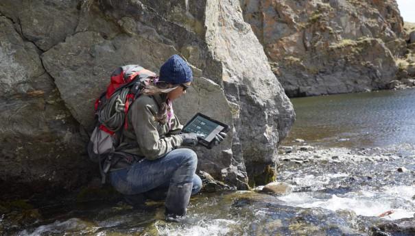 Woman Kneeling in Creek with Latitude 12 Rugged Tablet
